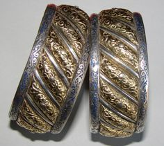 "A splendid antique pair of ""shams wa qamar"" bracelets.This is a fine, unusual pair of ""sun and moon"" bracelets, most likely from the former imperial city of Meknes. Notice the wide gold repousse panels flanked by thin, fine silver ones. There is blue enamel along the edges. Posted by Ethnic Embellishments."