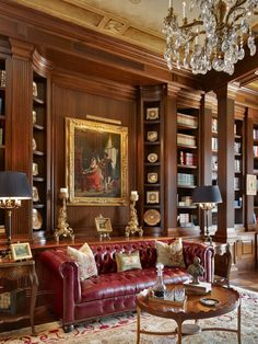 A red Chesterfield for an exclusive luxury home library with dividing space square pilasters, lots of reeded carvings and plenty of shelve space.