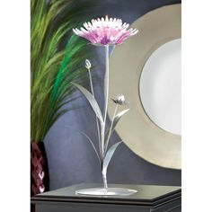 Gorgeous pink lotus flower in full bloom supports a single tealight at its center in this dramatic tabletop candle holder. Its silver base rises up with elegant leaves and baby flower buds in clear an