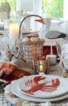 Dining With The Seagulls | http://betweennapsontheporch.net/nautical-table-setting-tablescape-with-lobster-crab-plates-and-fishnet-tablecloth/