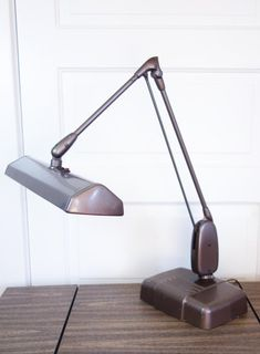This vintage industrial desk lamp is an iconic mid century piece that is still one of the best desk lamps you can find! It is a Dazor Floating Fixture model 2324. Use it in your Work from Home office, studio, or craft room.The light swivels and adjusts to any height. It has a heavy base with indentations for pens or pencils. It has a wonderful bronze brown finish and has a tag on the back from the Florida State University. Industrial Desk, Vintage Industrial, Tanker Desk, Christmas Dinner Plates, Best Desk Lamp, Vintage Home Decor, State University, Small Businesses