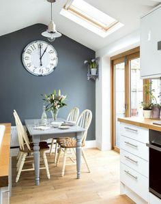 peinture bleu canard, cuisine bleu canard, plafond en forme triangulaire, meuble blanc, fenêtre au plafond et portes coulissantes pour beaucoup de lumière, table gris clair, quatre chaises en couleur crème et marron clair, grande horloge de style ancien eu mur peint en bleu canard