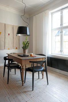 Panelovnen fulgte med leiligheten, og for at den skulle passe best mulig inn med resten av interiøret har den blitt lakkert i svart. Taklampene er fra Ikea, mens stolene CH20 fra 1956 er laget av hans J. Wegner for Carl Hansen og Søn, Illums Bolighus.