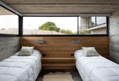 sol en béton ciré, lambris mural en bois massif et lit simple design