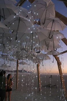 """Curtain lights become """"rain"""" at this Burning Man installation. Wonderful idea for a baby shower! See our curtain lights: http://www.lightsforalloccasions.com/c-238-curtain-lights.aspx Umbrella Decorations, Umbrella Centerpiece, Umbrella Lights, Umbrella Art, Umbrella Jellyfish, Festival Decorations, Wedding Decorations, Light Decorations, Art Festival"""