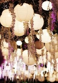 Paper lanterns and flowers hang from ceiling at wedding reception