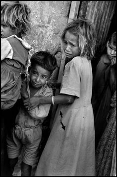 Burt Glinn -  ISRAEL. El Arish. 1956. On the 3rd day of the war, frightened Arab children watch Israeli troops move through their town to the Suez Canal during the Sinai campaign.
