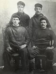 Studio portrait of four young fishermen. Two wear ganseys, and two sailors' canvas smocks (note no buttons). Also note their leather boots and clay pipes. Probably taken between 1900-1915
