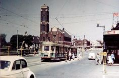 Traffic in Oxford Street ... 1957 ... Looking E along Oxford Street from corner of Flinders Street at Taylor Square. ... View towards the Sacred Heart Church on the corner of Darlinghurst Road and Victoria Street. Showing tram, cars, pedestrians & overhead power cables. The Albury Hotel is in distance on R. ... Len Stone / Vic Solomons Collection: 194 ... City of Sydney Archives