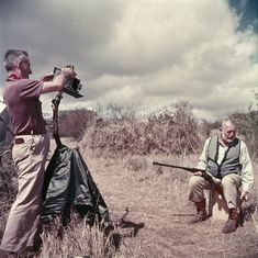Ernest Hemingway sitting and holding a rifle while photographer Earl Theisen takes his photograph in Africa. 1953