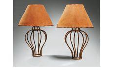 Jean Royère (1902-1981) Paire de lampes en fer forgé à patine dorée (en partie d'origine), à montants ajourés et galbés formant cage. Abats-jour d'époque en peau couleur chamois lacés de cuir. H : 42, 5 cm, D : 30 cm CM