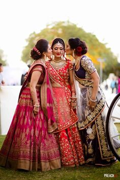 Sister of the Bride - Bride in a Red Bridal Lehenga and Sisters in a Pink Lehenga with Gold Hand Painted Work, Navy Lehenga with Gold Embroidery #wedmegood #indianwedding #indianbride #lehenga #gold #navy #pink #red #sisterofthebrideoutfit #sisterofthebride