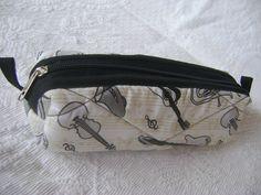 Nécessaire confeccionada com tecido 100% algodão e forrada com nylon. <br> Mede aproximadamente 19cm de largura, 5cm de altura e 7cm de profundidade.
