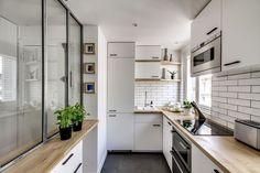 Une petite cuisine entre blanc et bois clair avec une verrière d'atelier en bonus
