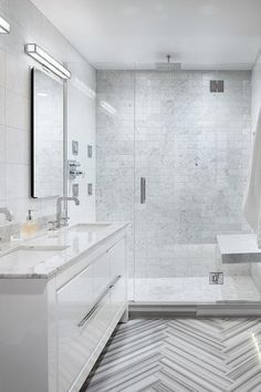 Modern bathroom features a white lacquer vanity topped with grey and white marble fitted with his and hers sink and frameless medicine cabinet alongside a gray marble chevron tiled floor.