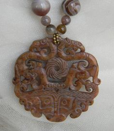 Jade dragon pendant w Botswana agate beads necklace w beaded jewelry. Jade double dragon pendant necklace. Stunningly beautiful Chinese carved Jade pendant of fine quality and workmanship, richly hand carved with intricate details, in warm caramel / brown sugar color with gemstone necklace. The pendant has carvings of dragons, amulets of heavenly power and protection and longevity in Chinese mythology.  The necklace has large Botswana agate beads with swirls and clouds of color with lines…