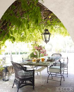 An antique hanging lantern, and vintage wicker and iron chairs on the terrace of Reese Witherspoon's Ojai home