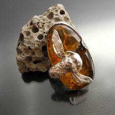 Srebrna broszka (także zawieszka) z bursztynem i srebrną pszczołą, która pracuje nad zbudowaniem plastra miodu.