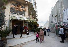 """O """"The Walled Off Hotel"""" abriu as portas na manhã desta sexta-feira para a imprensa. Localizado em Belém, na Cisjordânia, o local está repleto de obras do artista de rua Banksy e conta com 9 quartos, todos com a """"pior vista do mundo"""". Localizado bem em frente ao famoso muro construído por Israel para impedir a entrada de """"""""""""terroristas"""""""""""" palestinos na cidade, um dos maiores destaques do local vai para o quarto número 3, que possui um quadro onde um israelense e um palestino duelam em uma…"""