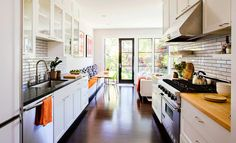 KITCHEN: Glass-front cabinets, floating shelves, a pull-out pantry, and bright white surfaces make the kitchen feel extra big.