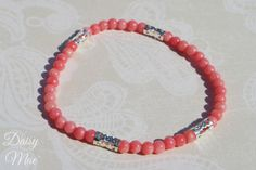 Pink Coral Bracelet - $5 I kind of like this one--inexpensive, and natural coral beads so maybe less likely to clash with other coral shades.  (Natural materials often contain subtle color variations making them less likely to clash.)  Can be custom ordered in a shorter size.