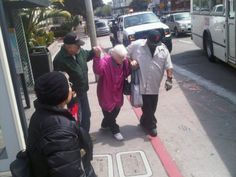 Two men helping an old lady cross