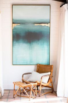 A gold and blue abstract art piece hangs from a white shiplap foyer wall above a rattan lounge chair with a matching ottoman placed on terracotta floor tiles beside a window dressed in white curtains.
