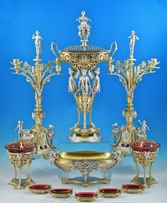 A six piece parcel-gilt sterling silver table garniture by Elkington, Birmingham 1871-1875. with red glass liners.