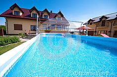 Luxurious house backyard with big swimming pool with volleyball net.