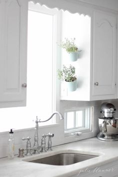 """Angling pots over the sink makes use of ample kitchen window light (and the """"short wall"""" on the side of a cabinet). See more from Julie Blanner »   - HouseBeautiful.com"""
