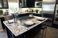 Arctic White granite + dark cabinets + slate tile + stainless steel appliances