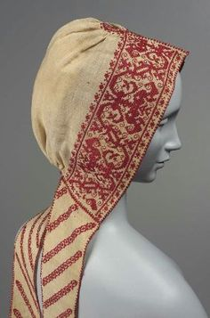 Cream colored linen with a band of conventional ornament around the face worked with red silk in long-armed cross stitch. Narrow diagonal bands also worked with red silk decorated lappets. 19th-century reproduction of 17th century cap