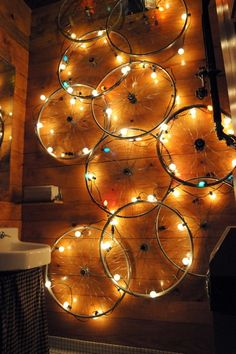 Bicycle rims with lights create easy art for the wall! Looks like they are using G30 or G40 Globe Light Sets. Clear, satin and multi colored satin options available online at http://www.partylights.com/String-Lights-Sets/C7-Globe-Light-Sets.
