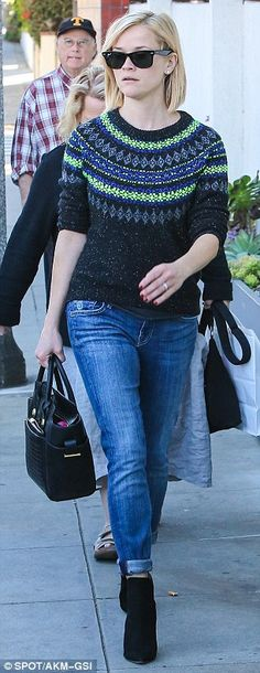 Effortlessly chic: The 37-year-old looked festive in her black, blue and fluoro green sweater, which she paired with cuffed jeans and black ...