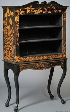 A Victorian [black] painted cabinet-on-stand, late 19th century, upper section with scrolled crest centering a shell motif with gold painted foliate vines above three shelves, sides and bottom with further gold painted foliage, raised on a stand with a central frieze drawer with a painted monogram, and on four deeply curved cabriole legs terminating in claw and ball feet.