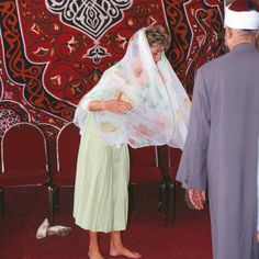 13 May 1992: Princess Diana removes her shoes and coveres her hair appropriately with a floral silk scarf during a tour at Al Azhar Mosque in Cairo, Egypt