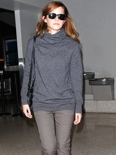 Emma Watson looks airport chic in a cozy gray sweater as she departs Los Angeles International Airport on Friday. (oct 2014)
