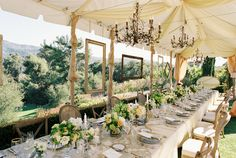 Elegant tablescape - hanging frames, chandeliers, low centerpieces in white.  Click www.Signature-Event.com to assist with your wedding details.  Wedding and Event Planning.