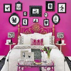Parede rosa choque com molduras pretas e ornamentadas.