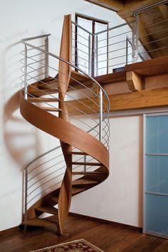 VANIA. Spiral staircase in solid wood. Wrapping line rail H mm.29 with step fastening from inside, no visible screws. Wooden helical solid newel. Diameter from 130 to 200 cm.
