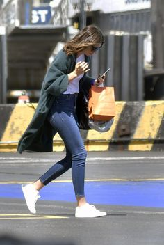Miranda Kerr wearing Are You Am I Rylie Baby Tee, Hermes Birkin Bag in Black, Saint Laurent Sl1 Sunglasses, Common Projects Original Achilles Leather Sneakers and Miranda + Mother Denim Audrey Jean Absolutely Positively