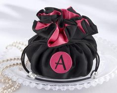 """""""The Cosmopolitan"""" Monogrammed Jewelry Pouch made of easy to clean black polyester with a pink satin lining. The bottom of the pouch is padded for extra protection. Inside there are eight pockets to hold earrings, bracelets, necklaces, or any other valuables.  It sinches closed with two pull strings. You can personalize this item with a monogram snap on pink button."""