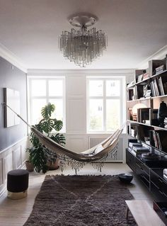 In a room for reading, an elegant hammock puts in a surprise appearance over a Moroccan Beni Quarain Rug. Vitsoe shelving and a Studioilse Low Bench that can be used as a step stool maintain organization across the wall.