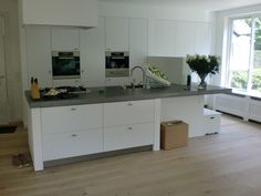 keuken blad van beton, een witte keuken met mooie grepen en een houten vloer...