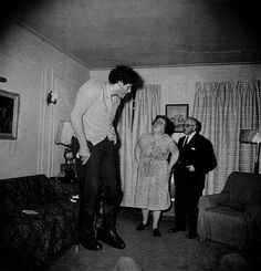 "A Jewish Giant At Home With His Parents in the Bronx, New York, 1970 -- Diane Arbus said: ""Most people go through life dreading they'll have a traumatic experience. Freaks were born with their trauma. They've already passed their test in life. They're aristocrats."""