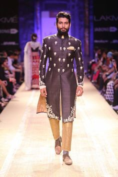 Black and gold Indian men's sherwani by Anju Modi at Lakme Fashion Week Winter 2014. More here: http://www.indianweddingsite.com/lakme-fashion-week-winter-2014-anju-modi-collection/