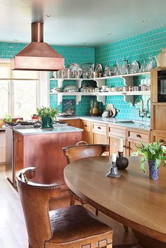 Turquoise subway wall tiles, Copper island and hood (Stainless steel gas range) warm salvaged wood, white open shelves, and Carmel leather studded 'western' chairs around a long oval table.