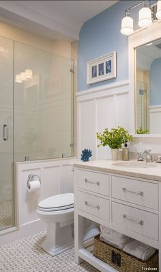 A beautiful bathroom with light blue walls, a single vanity with storage and glass shower doors. Click to see bathroom remodeling costs and get free quotes from local pros!