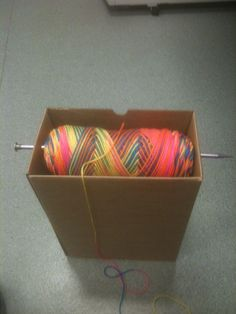 Ingenious!  Unfortunately can't link it to the website as it was 'spam', but this is simply a box with a knitting needle through it, whilst holding your yarn.  Simple and FABULOUS!!
