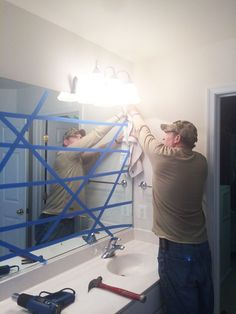 How to safely and easily remove a large, builder bathroom mirror that is glued on the wall.